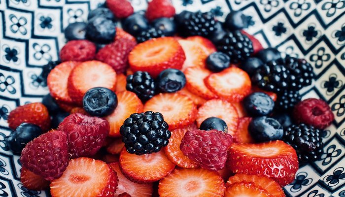 Blueberries, blackberries, raspberries and sliced strawberries in a patterned bowl to represent superfoods